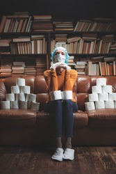 Woman with protective antiviral mask and a reserve of toilet paper waiting anxious in home isolation.