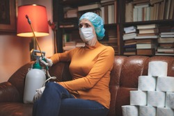 Woman with protective antiviral mask, chemical decontamination sprayer bottle and a reserve of toilet paper waiting anxious in home isolation.