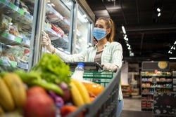 Woman with protective mask and gloves shopping in supermarket during COVID-19 pandemic or corona virus. Protect yourself against highly contagious coronavirus. Female in grocery store.