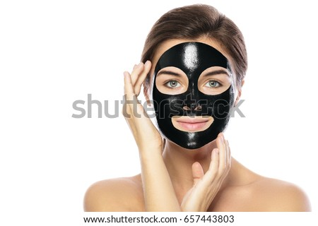 Woman with purifying black mask on her face isolated on white background #657443803