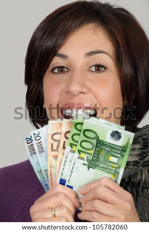 Woman with purple jacket and gray scarf with with euro bills
