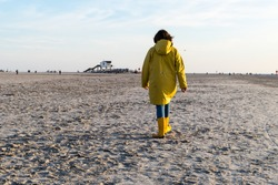 Woman with Raincoat walking on Beach of St. Peter-Ording Germany