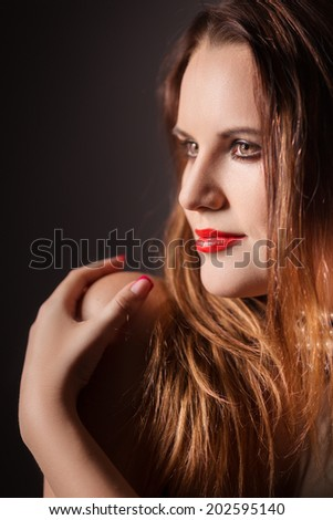 woman with red fluffy hair embraced herself