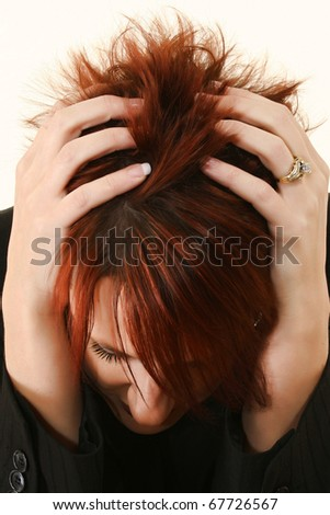 Woman with red hair and manicured hands in hair stressed or with headache or sad.