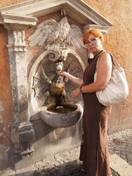 woman with red hair wearing glasses and a brown sundress washing her hand by a street fountain in Rome