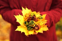 Woman with red jacket holding hand made maple leaf rose flower, autumn concept