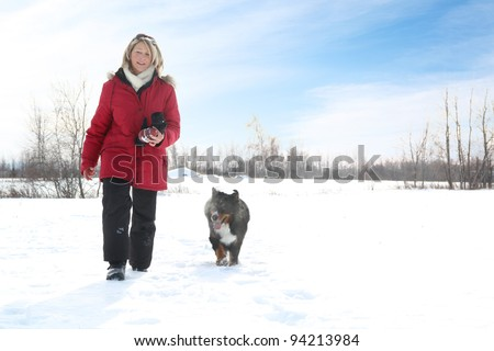 Woman with red jacket walking during winter with her dog - stock photo