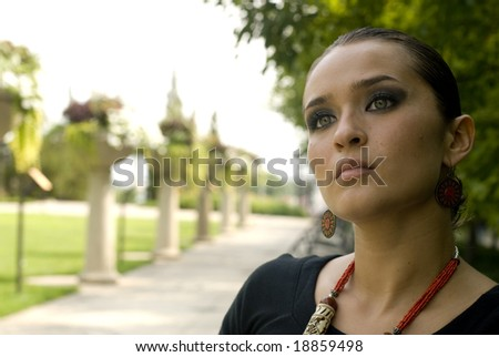 Woman with red jewelry sitting in a park on a sunny day