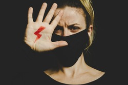 Woman with red lightning bolt drawn on her hand, symbol of the National Women's Strike against the tightening of the anti-abortion law in Poland. Wearing protective face mask against COVID-19 Coronavi