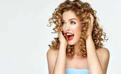 Woman with red lips and nails shouts in surprise ,and joy.Beautiful girl  with curly hair surprised and shocked   screaming with delight . Presenting your product. Expressive facial expressions