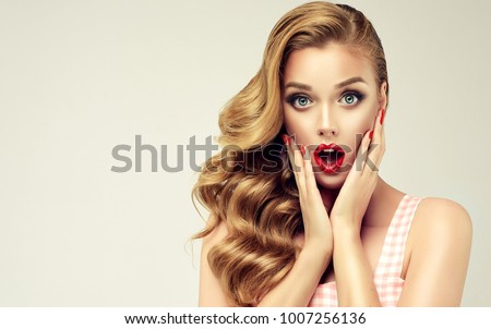 Woman with red lips and nails surprise holds cheeks by hand .Beautiful girl  with curly hair surprised and shocked looks on you . Presenting your product. Expressive facial expressions #1007256136