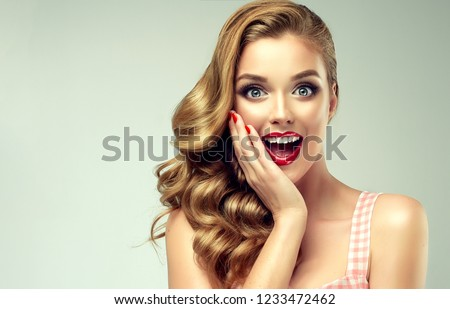 Woman with red lips and nails surprise holds cheeks by hand .Beautiful girl  with curly hair surprised and shocked looking on you . Presenting your product. Expressive facial expressions #1233472462
