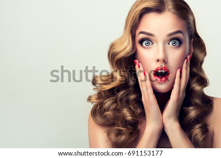 Woman with red lips and nails surprise holds cheeks by hand .Beautiful girl  with curly hair surprised and shocked looks on you . Presenting your product. Expressive facial expressions #691153177