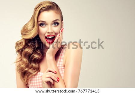 Woman with red lips and nails surprise holds cheeks by hand .Beautiful girl  with curly hair surprised and shocked looks on you . Presenting your product. Expressive facial expressions #767771413