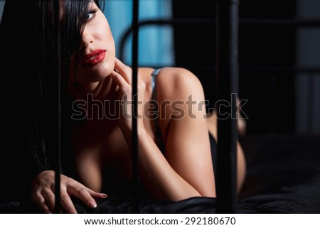 Woman with red lips in lingerie flirting on black bed in a very sexual way