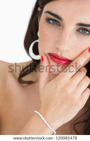 Woman with red lips touching her face while staring at camera