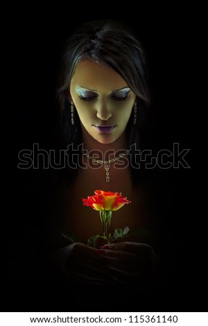 Woman with red rose in the shadows