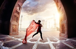 Woman with red scarf dancing near Taj Mahal in Agra, Uttar Pradesh, India