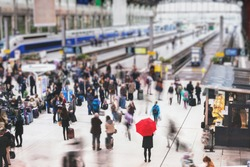 woman with red umbrella waiting at train station and blurred people in motion, solitude concept