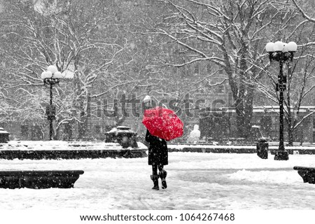 Woman with red umbrella walking through black and white landscape during nor'easter snow storm in Washington Square Park, New York City
