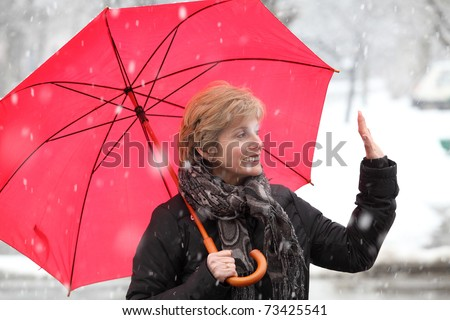 Woman with red umbrella waving  in a winter day while snowing