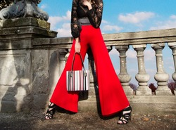 Woman with red wide pants holding the handbag purse on the bridge. Fashion shoot.