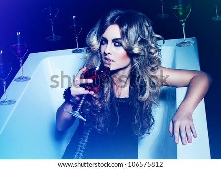 woman with red wine and other glasses in bath