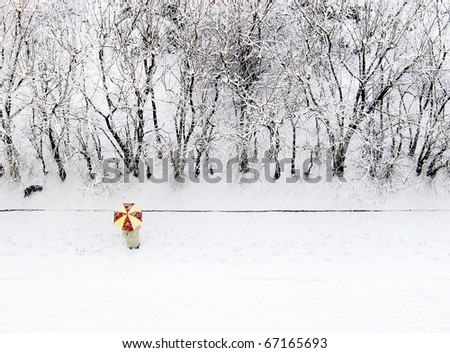 Woman with red & yellow umbrella on white snowy background, bird's eye view