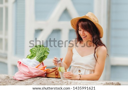 Woman with reusable water bottle  and  bamboo handbag, cotton grocery bag with vegetables.  #1435991621