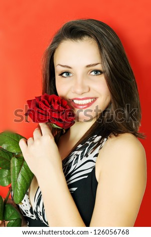 Woman with rose on a red background - stock photo