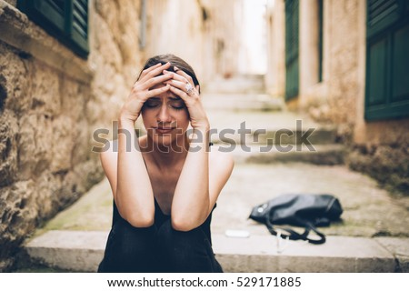 Woman with sad face crying.Sad expression,sad emotion,despair,sadness.Woman in emotional stress and pain.Woman sitting alone on the stairs, after a fight with a boyfriend.Relationship and love problem