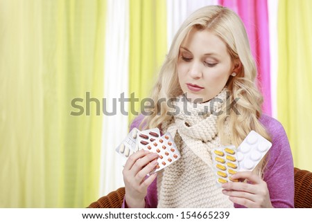 Woman with scarf decides between different pills