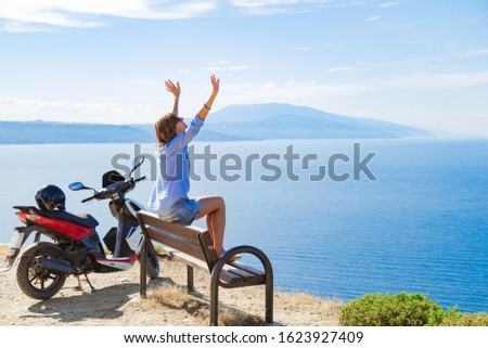 Woman with scooter looking at the distand sea horizon.