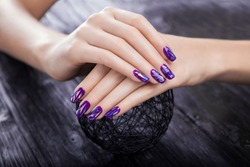 Woman with shattered glass purple manicure holds a ball on black wooden background