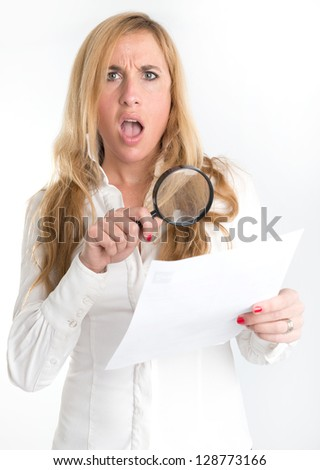 Woman with shocked expression examining a document through a magnifying glass - stock photo