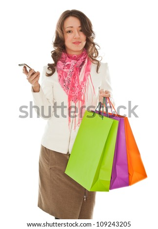 Woman with shopping bags calling by phone isolated on white
