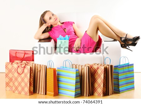 Woman with shopping bags having a rest on sofa