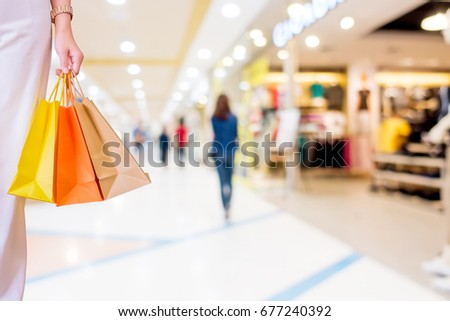 Woman with shopping bags in shopping mall, consumerism and sale concept.