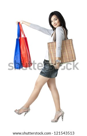 Woman with shopping bags posing over the white background