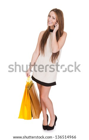 Woman With Shopping Bags Talking On Cell Phone Over White Background
