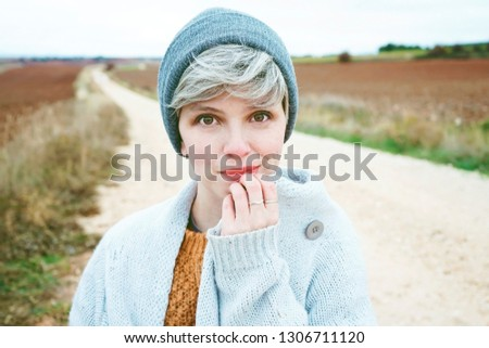 Woman with short and gray hair is alone in the beggining of a rural path in a cold autumn day                                #1306711120