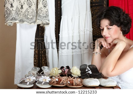 Woman with short brown hair sitting next to her shoe collection in her mid 30s, early 40s
