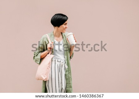 Woman with short hair holding reusable coffee cup and eco bag enjoying morning. Eco friendly concept. #1460386367