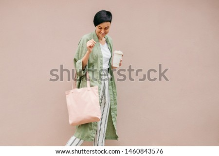 Woman with short hair holding reusable coffee cup and eco bag enjoying morning. Eco friendly concept. #1460843576