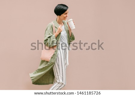 Woman with short hair holding reusable coffee cup and eco bag enjoying morning. Eco friendly concept. #1461185726