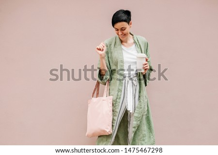 Woman with short hair holding reusable coffee cup and eco bag enjoying morning. Eco friendly concept. #1475467298