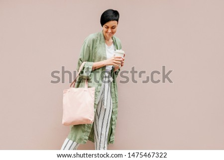 Woman with short hair holding reusable coffee cup and eco bag enjoying morning. Eco friendly concept. #1475467322