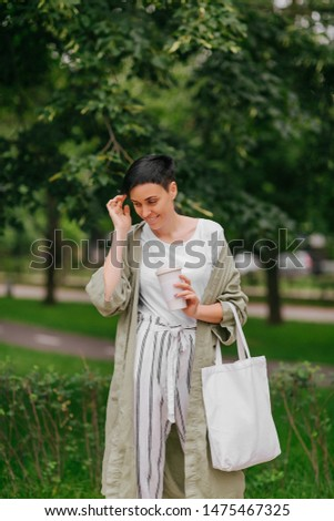 Woman with short hair holding reusable coffee cup and eco bag enjoying morning. Eco friendly concept. #1475467325