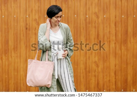 Woman with short hair holding reusable coffee cup and eco bag enjoying morning. Eco friendly concept. #1475467337