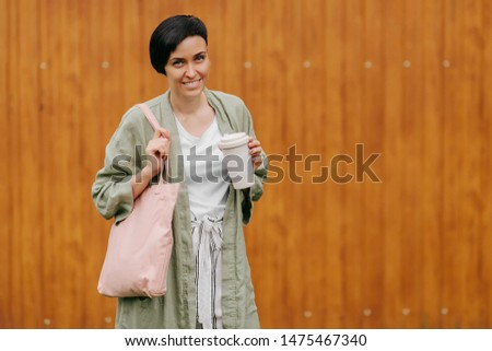 Woman with short hair holding reusable coffee cup and eco bag enjoying morning. Eco friendly concept. #1475467340